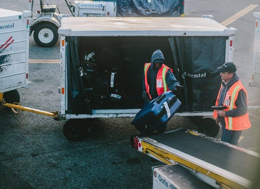 Baggage handlers loading bags onto airplane